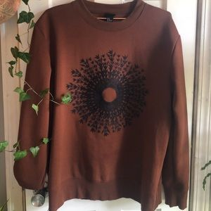 Dark Orange sweater with embroidered design.